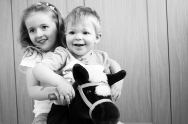 A brother and sister ride a toy horse for their family portrait photos.