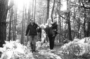 Two parents and their son and daughter walk through a wood during their winter UK portrait shoot.