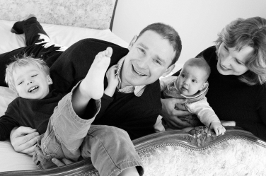 A family of four larks around on their bed during the professional family portraits.