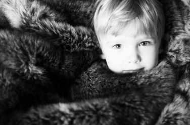 As snug as a bug in a rug: this boy is wrapped in up during his winter portrait session.