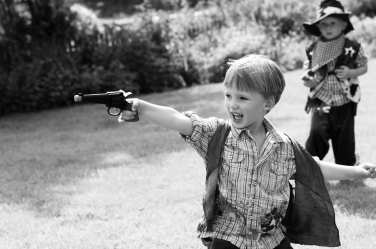 A small boy plays cowboys and Indians in a family shoot-out with photographer Helen Bartlett
