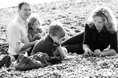 A family plays on a rocky beach together in a UK summer.