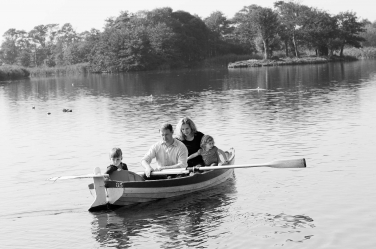 A family moment on the water with dad rowing and the son steering.