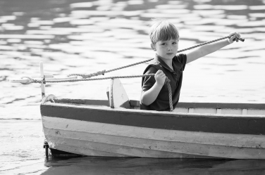A small boy is in charge of the boat carrying his family.