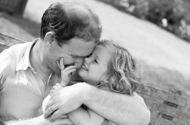 A dad snuggles his small daughter. This moment will live on forever in their lifestyle portraits.