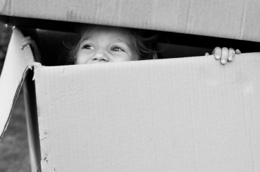 A box provides a playspace for this little girl during their family's lifestyle portraits.