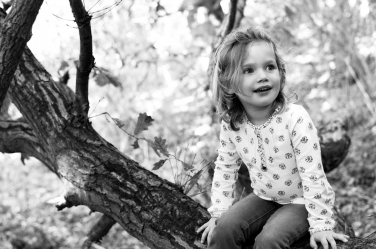 A black and white lifestyle portrait of a girl in a tree in London.
