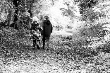 A black and white portrait of a brother and sister in autumn.