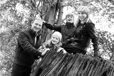 Trees provide a setting for this black and white family portrait.