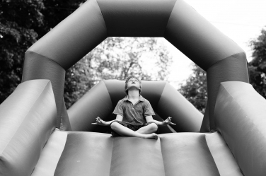 A zen moment on a bouncy castle for this boy in his family portrait shoot.