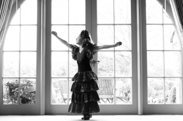 A girl dresses as a Spanish flamenco dancer, complete with castanets.