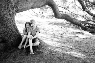 A brother and sister pose under a tree during a black and white portrait session.