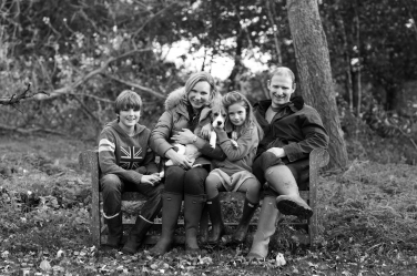 A family of four and their dog photographed on a garden bench.