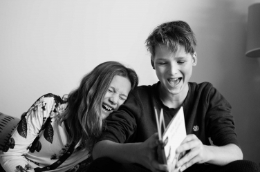 A teenage brother and sister giggle during a lifestyle family shoot in black and white.