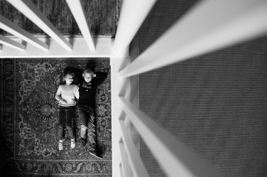 Two teenagers on a rug are framed by upstairs bannisters in this lifestyle teenage portrait by London photographer Helen Bartlett.
