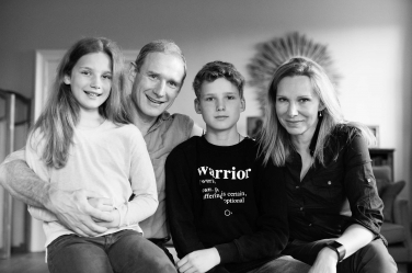 A family of four with two teenagers pose for family portraits as part of their lifestyle session in black and white.