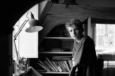A teenager in his room. The teen portrait is by London professional photographer Helen Bartlett.
