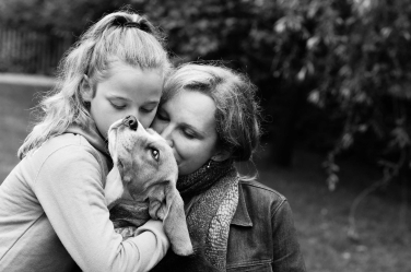 Mother, daughter and dog in a lifestyle family portrait.