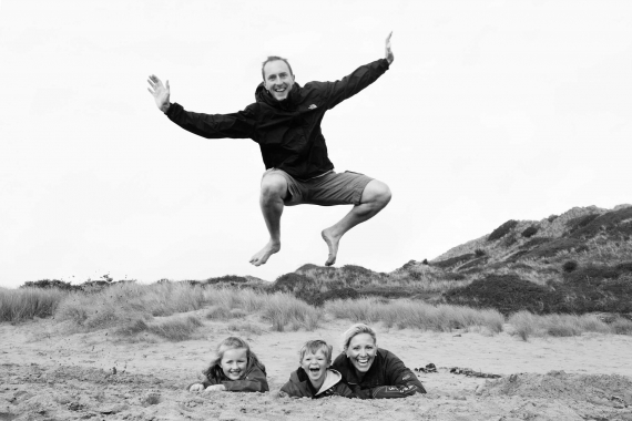A father leaps over his family during a family portrait session.