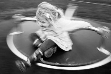 A little girl spins round on playground equipment during her family portraits.