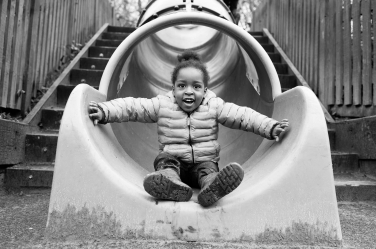 This black and white portrait is taken in a playground, with this little girl at the end of a slide.