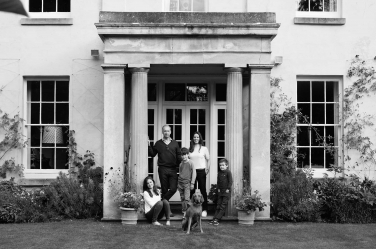 A family portrait taken in front of the family home, complete with dog.
