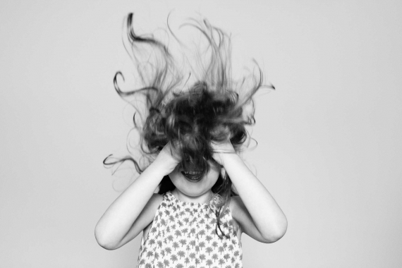 A little girl messes up her hair for this black and white portrait.