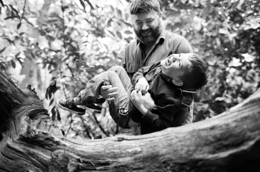 A father and son portrait taken with a background of leaves and branches.
