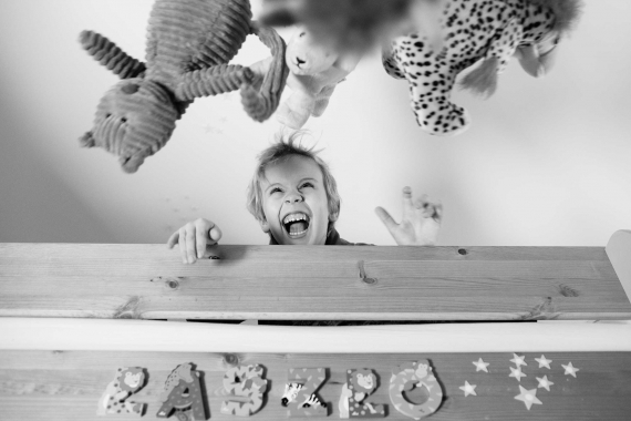 A small child giggles at airborne toys during a professional family photo shoot.