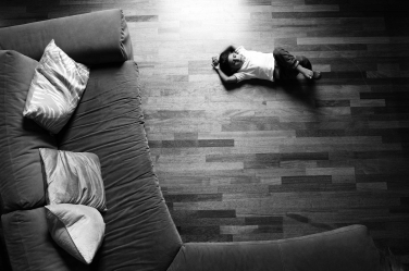 A black and white family photo of a small child on a wooden floor.