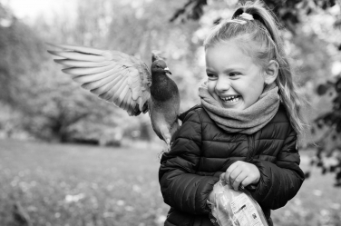 A pigeon alights near a small girl during a black and white professional portrait shoot in London.