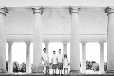 Large white columns and sunshine brighten this countryside family portrait of four siblings.