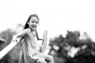 A black and white portrait of a little girl on playground equipment.