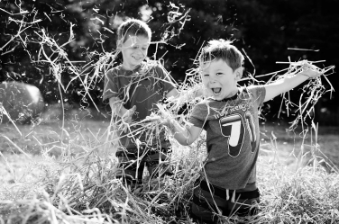 Two brothers throw hay into the air during an outdoor family portrait shoot.