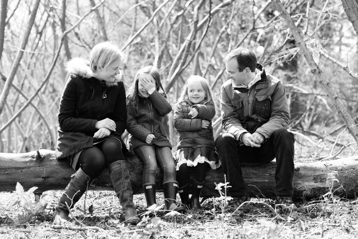 A black and white picture of a family of four on a log.