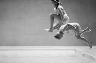 Brother and sister hurl themselves into a pool during a lively portrait photo session in London.