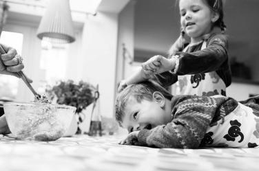 A sister attempts to roll her brother out like pastry, during a family cooking session.