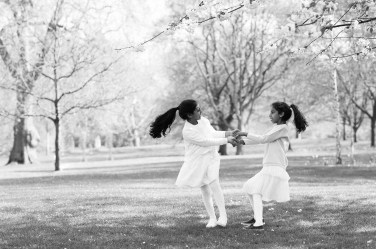 Two sisters dance through a park, long hair swinging, during a family portrait shoot.