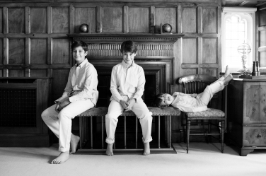 Three boys pose during a classic black and white family portrait shoot. They're seated around a fireplace with dark wooden surround.