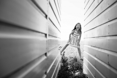 A girl plays between beach huts during family portraits at the beach.