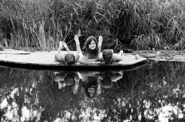 Three siblings on the side of a pond during a family portrait shoot in black and white. The lifestyle shoot for families is by London professional photographer Helen Bartlett.