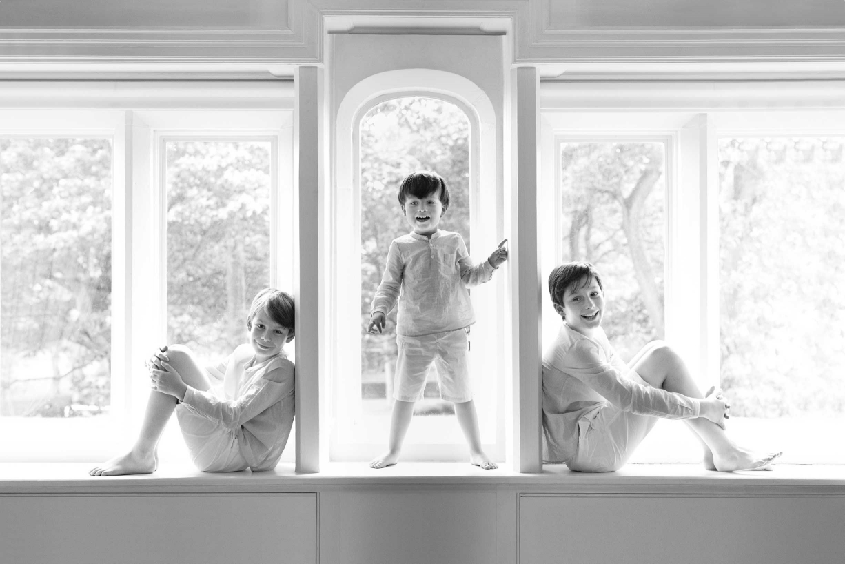 Three brothers pose for a family portrait in symmetrical window frames.