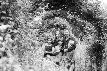 Two parents and their three children pose in a group portrait surrounded by garden foliage.