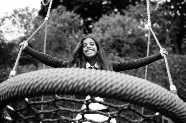 A teenager rocks herself in a large circular swing during a family portrait session.