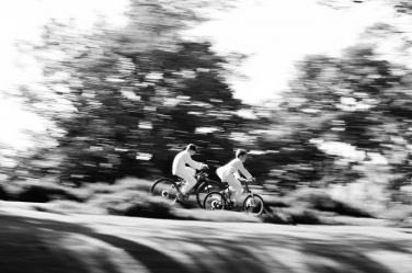 Two boys cycle quickly down a hill during a beautiful portrait session in black and white.