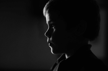 Rim light captures the silhouette of this little boy in a pensive moment.