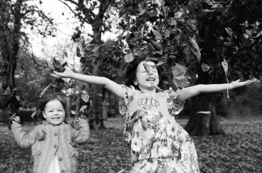 Two sisters throw leaves around during an autumn portrait shoot in London.