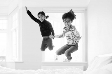 Siblings leap into the air during their portrait shoot.