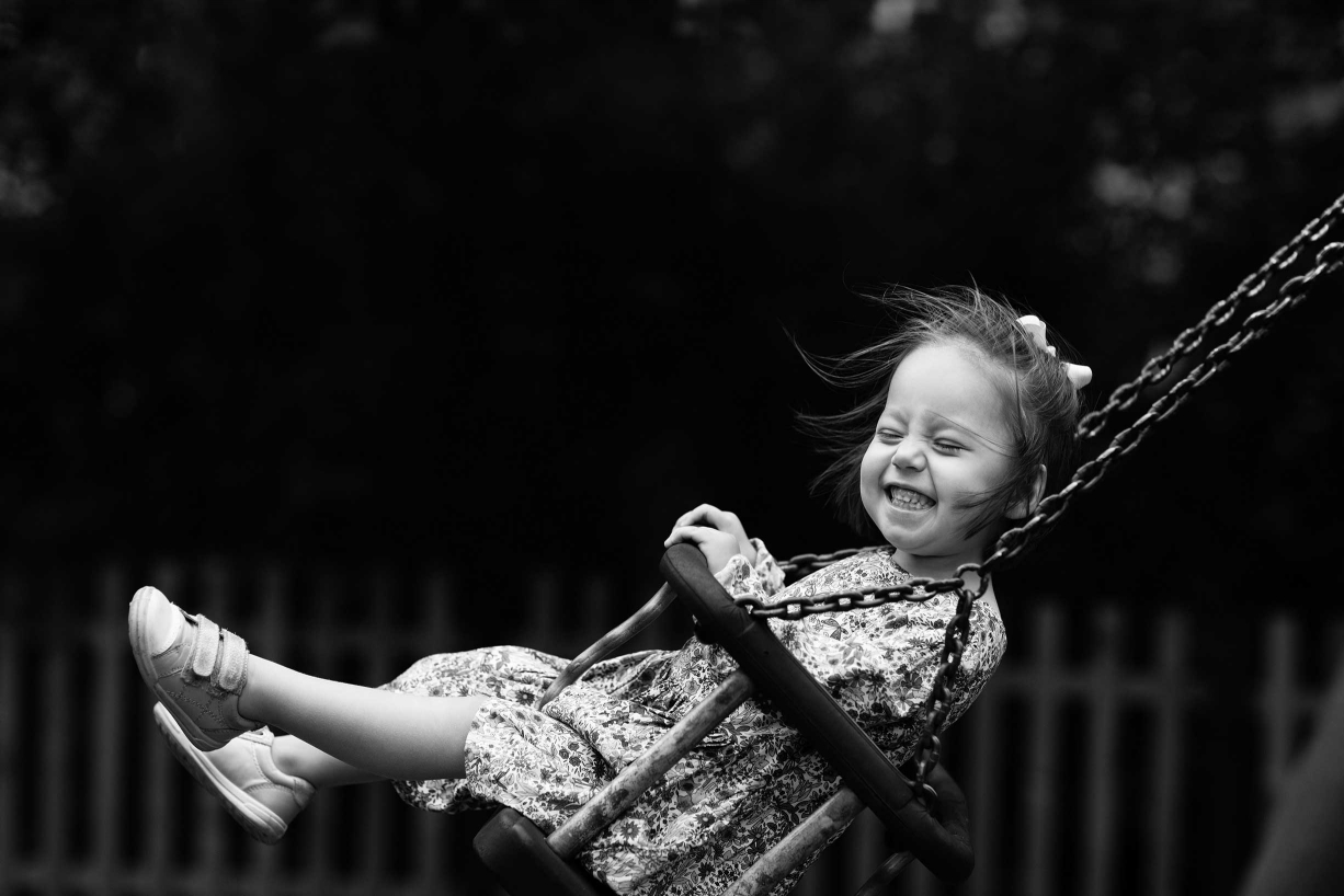 This little girl has a gleeful expression during being swung by her parents during a professional photo shoot.