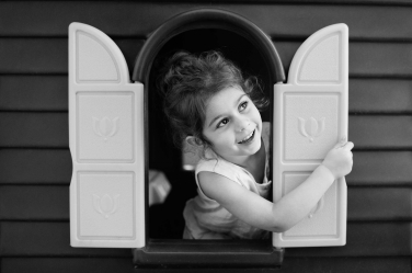 A photo of a little girl opening her playhouse windows to the world.